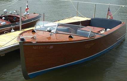 Two classic wooden runabout boats docked opposite on the same pier.